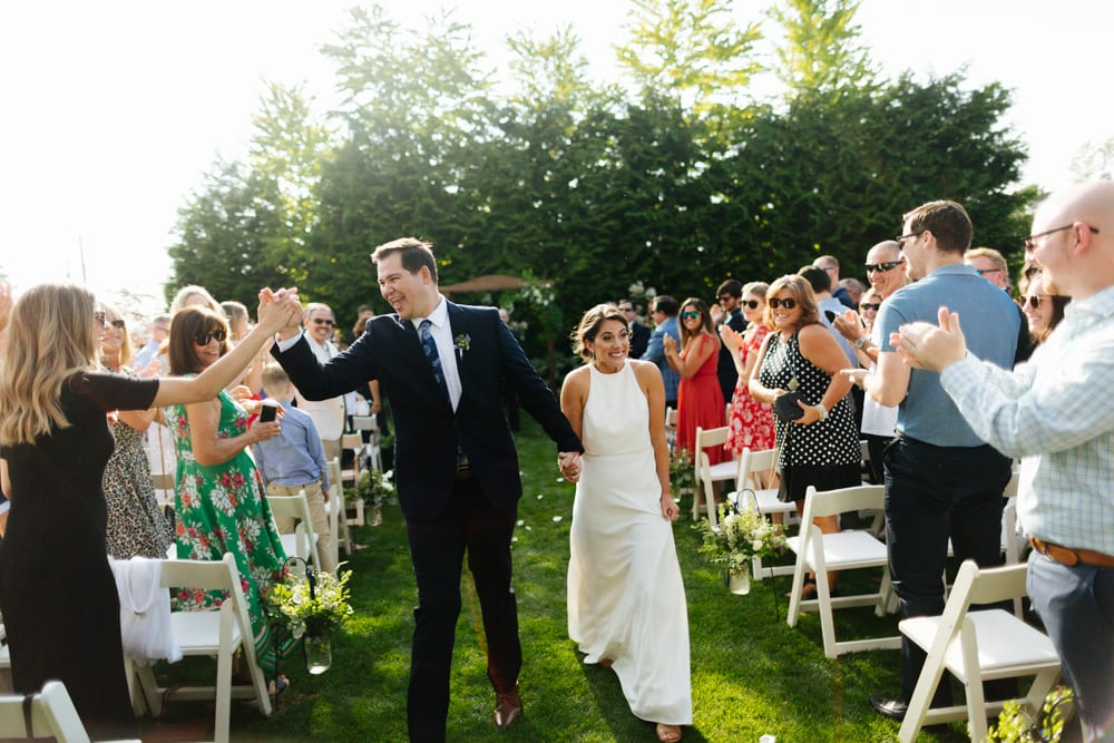 groom high fives after wedding ceremony pine creek nursery