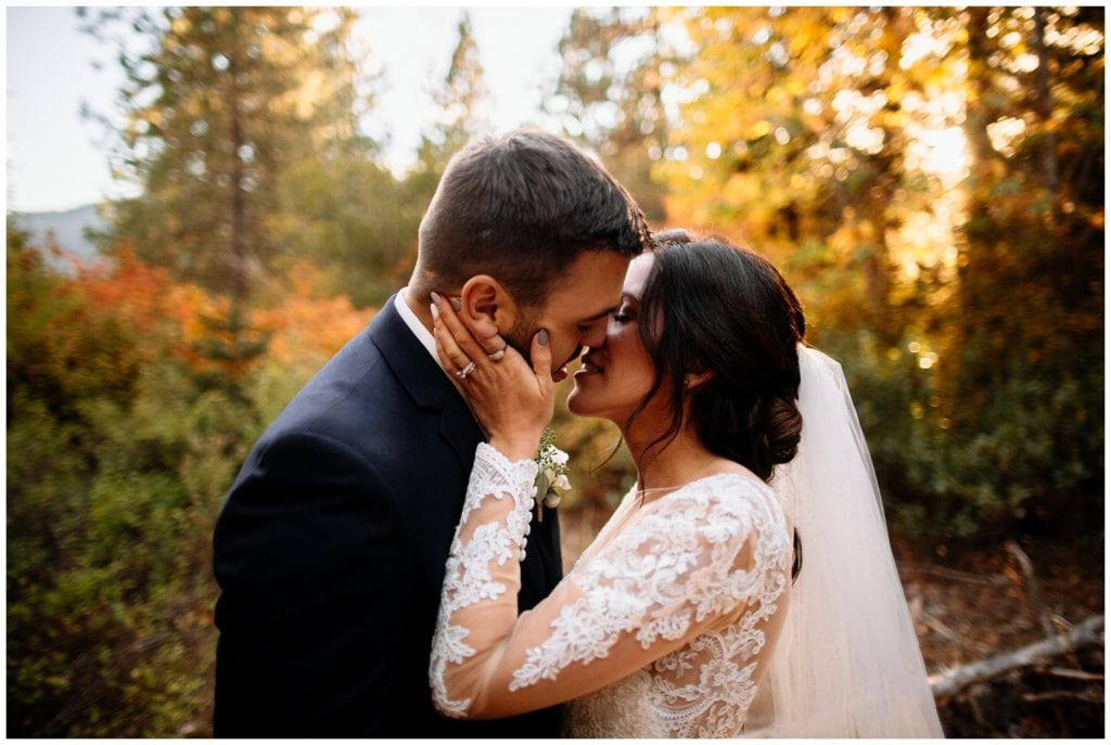 couple kisses beneath fall leaves brown family homestead wedding