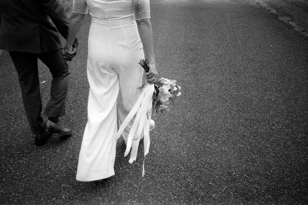 couple walks with bouquet on elopement