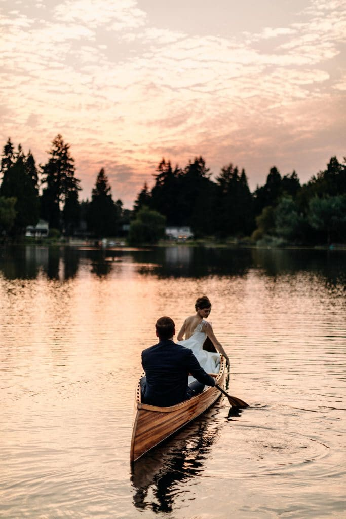 couple paddles away from elopement in canoe at sunset