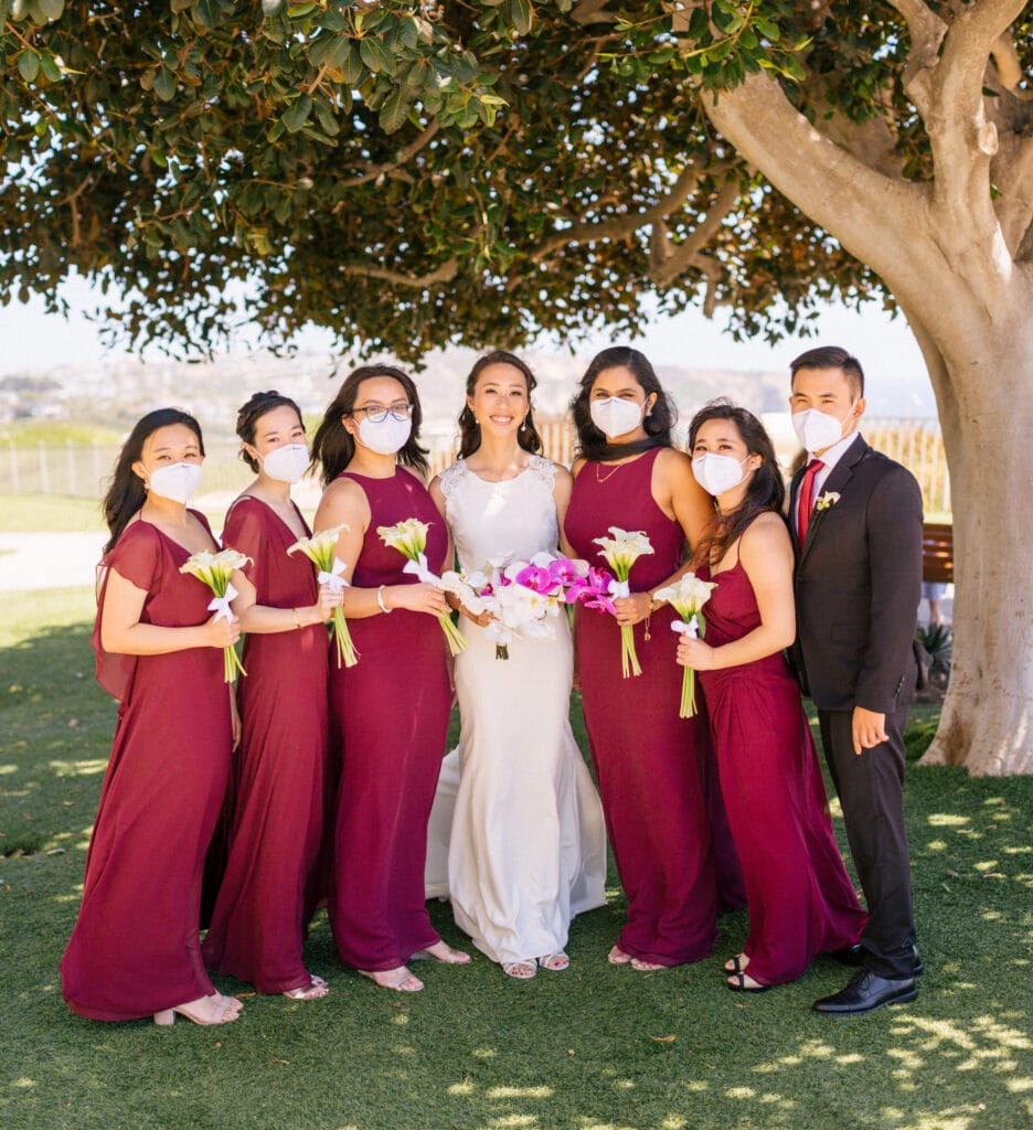 Bride with bridesmaids wearing kn-95 mask at COVID-19 wedding