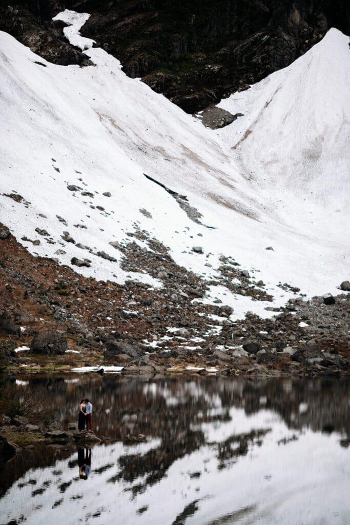 couple kisses during mountain lake elopement