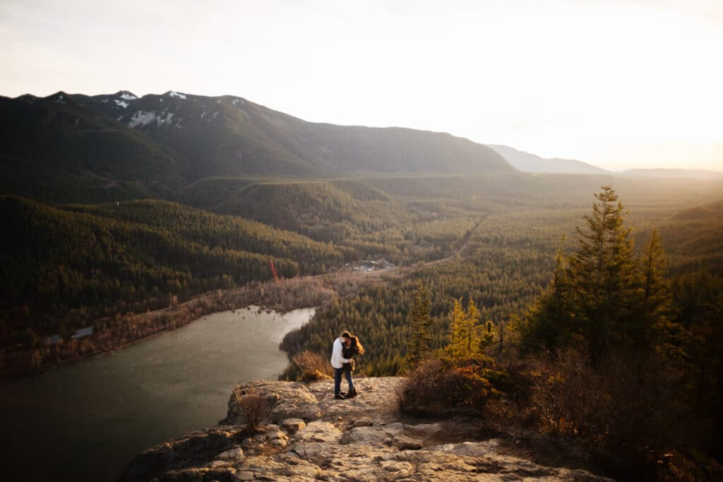 couple stands together during sunset mountaintop elopement