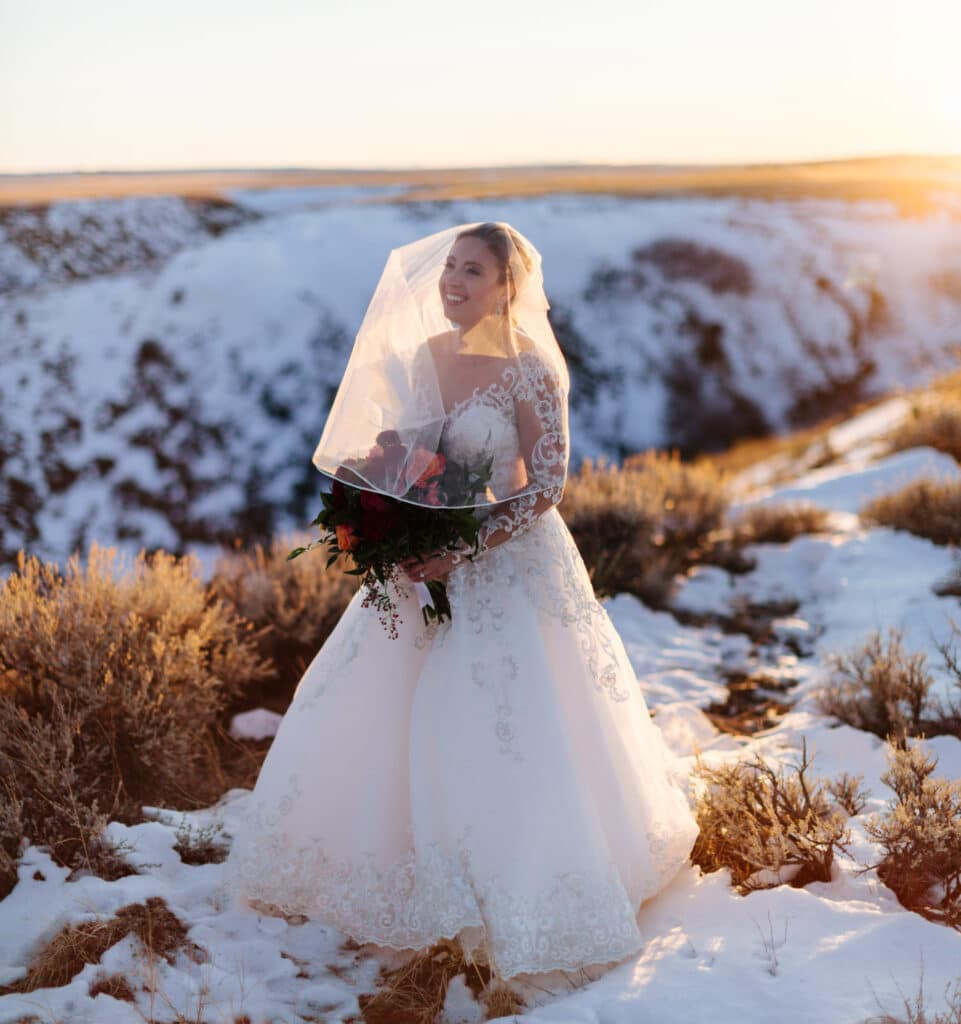 birde smiles on a snowy hill at sunset for her montana winter wedding