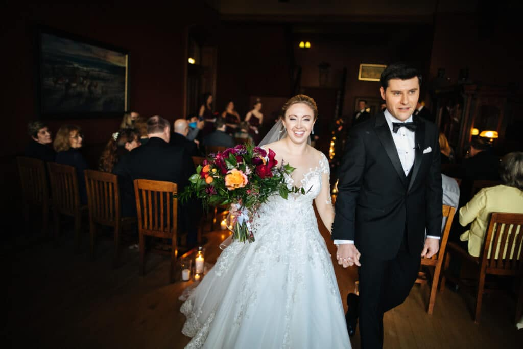 bride smiles and walks with groom back down aisle montana winter wedding