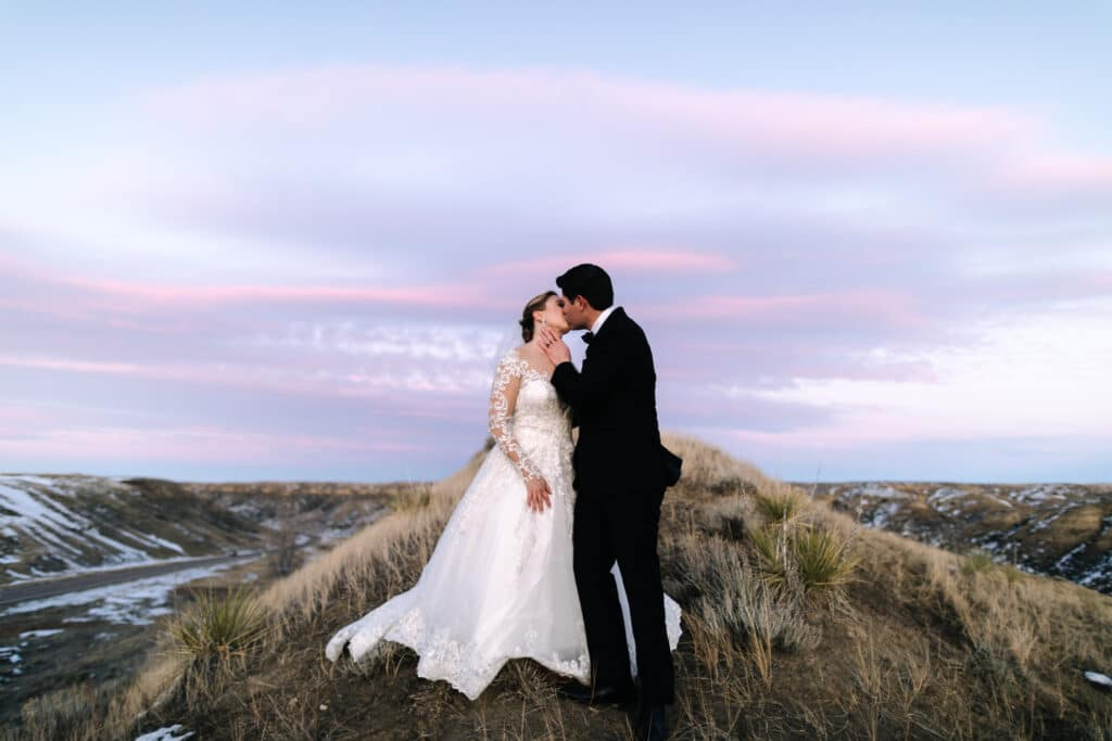 bride and groom kiss with pink sky at sunset during their montana winter wedding