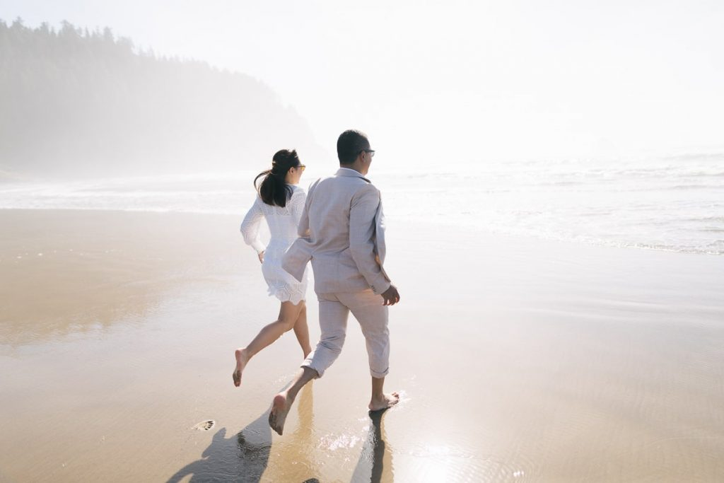 Bride and groom run into the ocean during oregon sunset ocean elopement