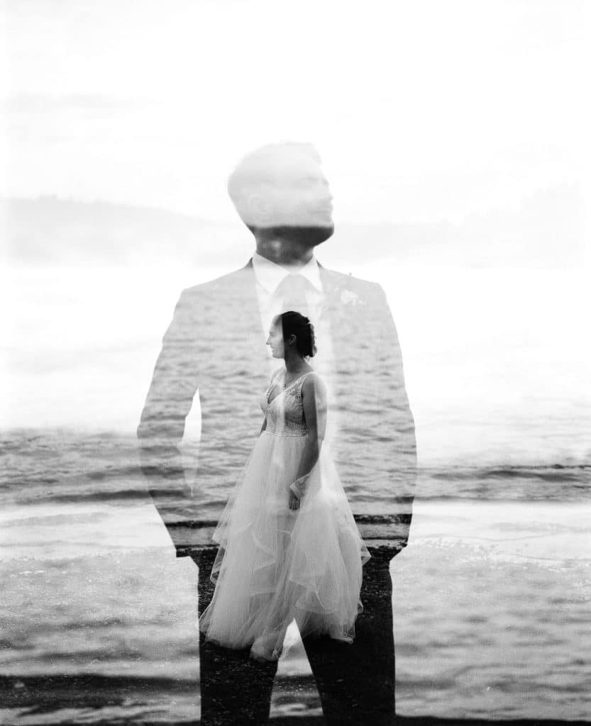 double exposure of bride and groom on black and white film during backyard elopement at sunset