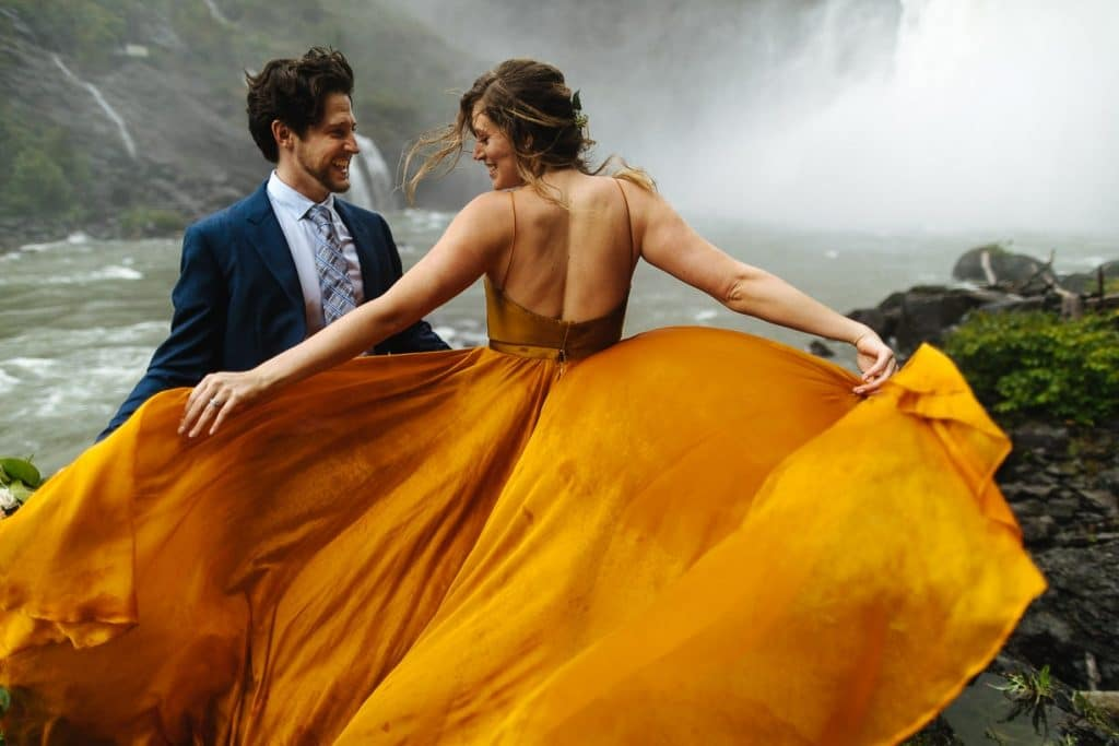 Groom and bride laugh while orange wedding dress is whipped in waterfall during washington state elopement