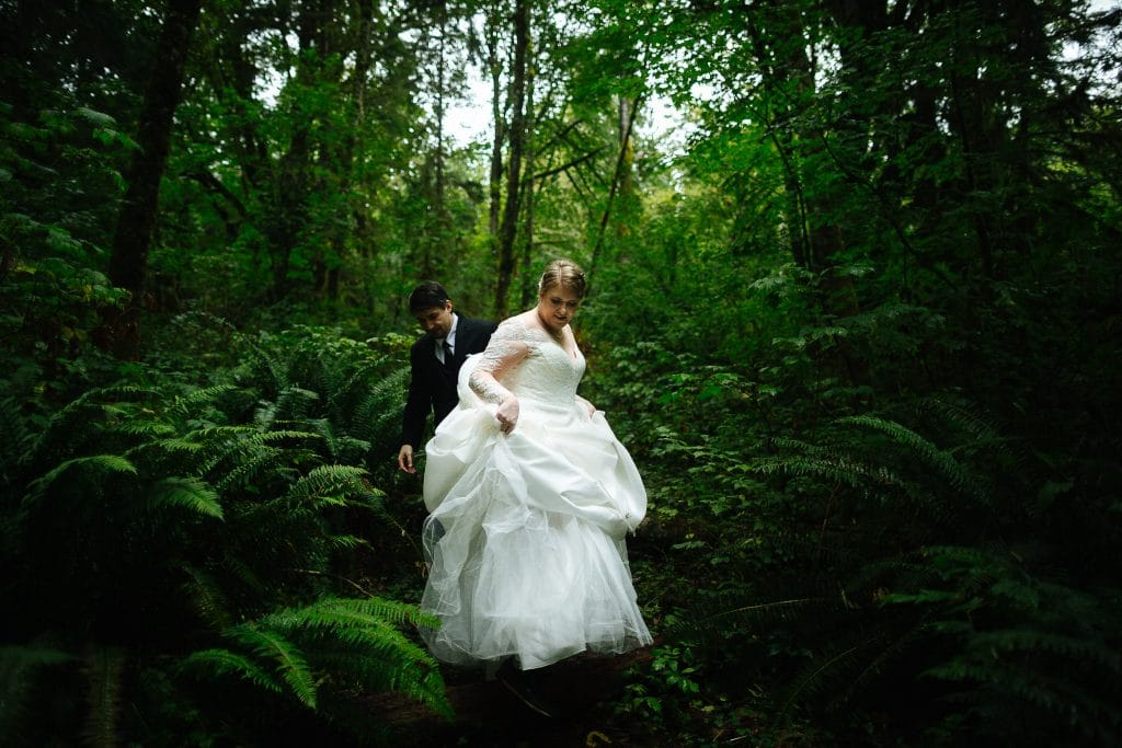 bride and groom walk through the woods during their washington state elopement at salish lodge