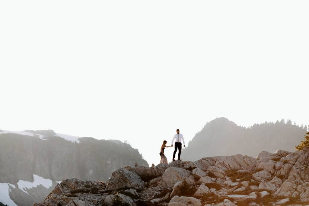 Couple climbs on rocks at Artist Point during north cascades elopement