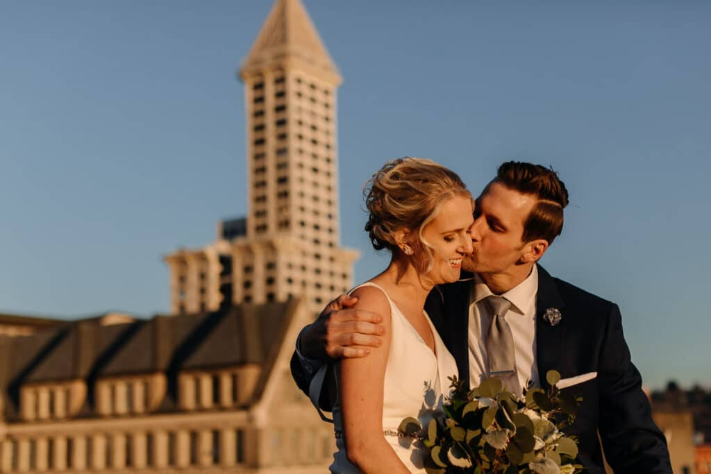 groom kisses bride on cheek in sunset during downtown seattle elopement