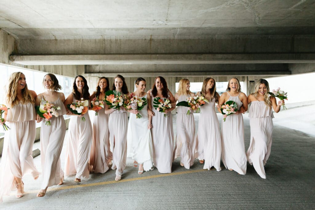 on rainy wedding day, bride and bridesmaids walk in a parking lot and laugh