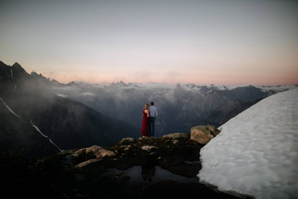 bride and groom stand together looking at mountains and sunset during north cascades elopement