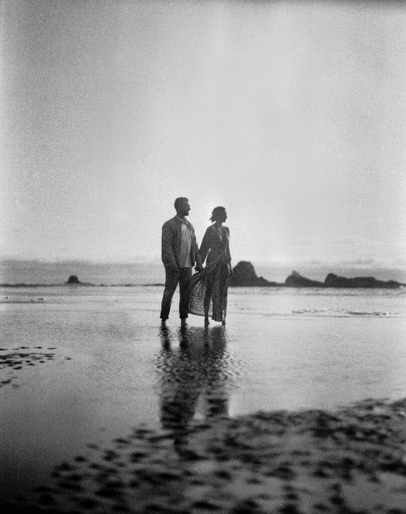 couple holds hands in sunset during ruby beach elopement