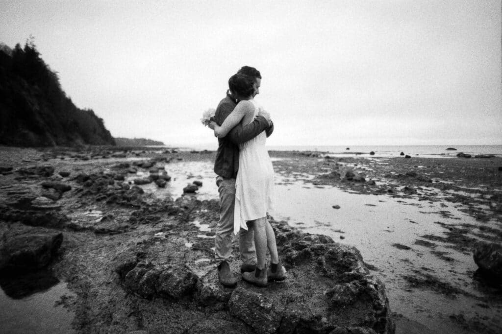 couple hugs on beach during whiskey creek elopement at olympic national park