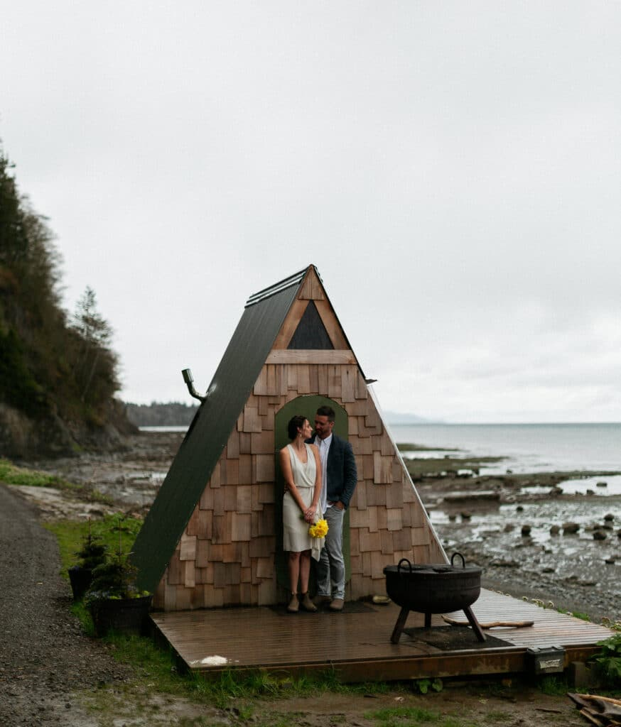 couple kisses in front of a frame during elopement