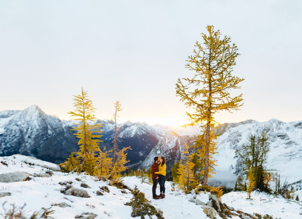 couple kisses in sunrise during hiking engagement session in the North Cascades