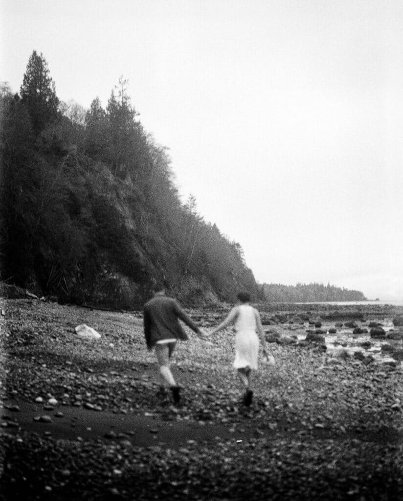 couple runs on the beach on film during olympic national park elopement