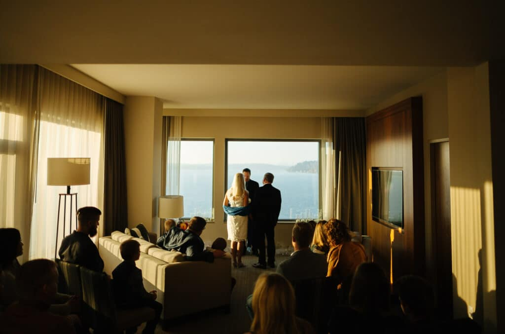 couple poses for elopement in hotel room on lake washington in seattle