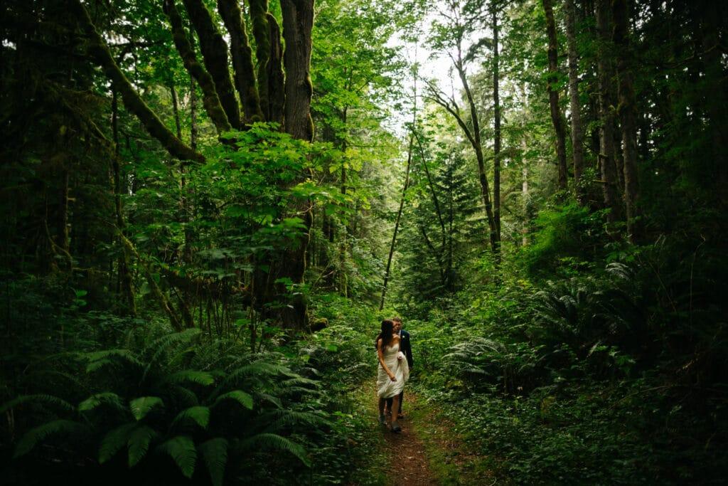 couple walks through hoh rainforest during elopement