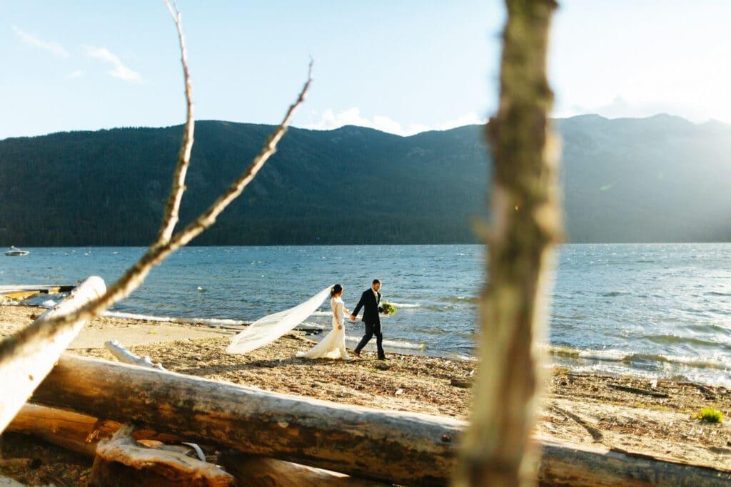 couple walks together along lake Crescent elopement