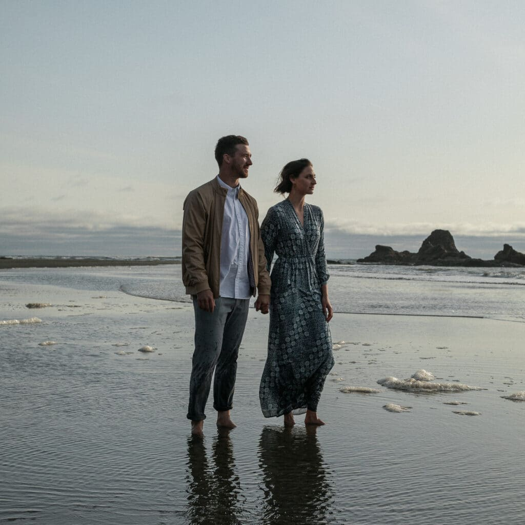 groom and bride hold hands and look at the sunset during olympic national park elopement
