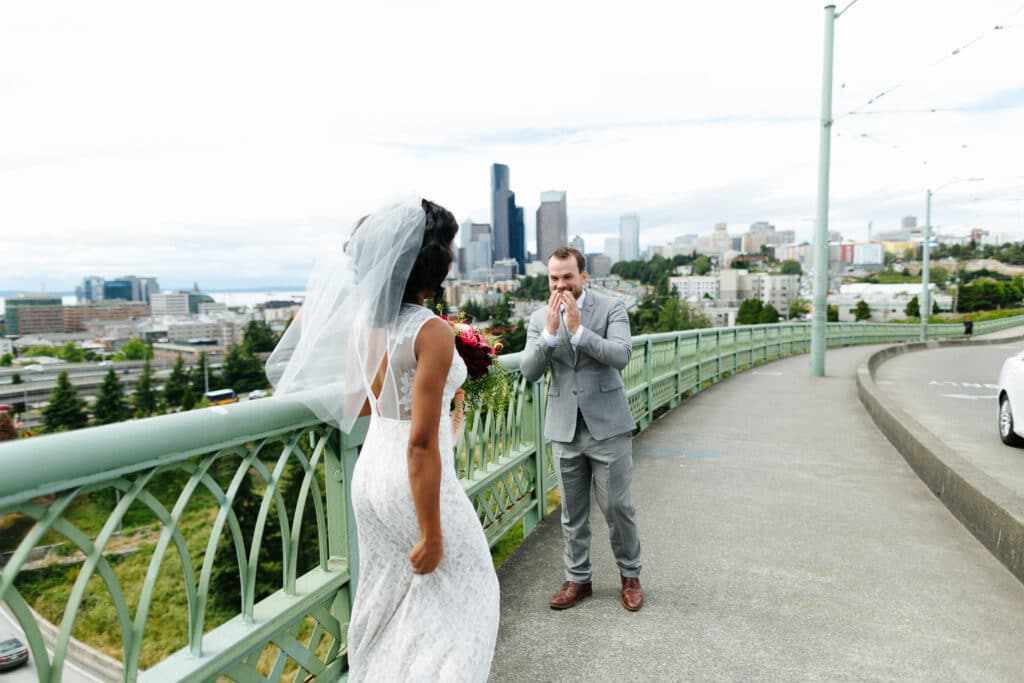 smiles at bride during first look on jose rizal bridge in downtown seattle on wedding day