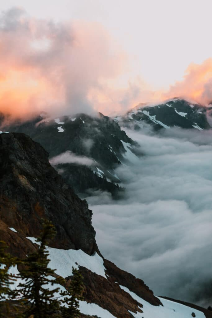 sunset on mountains with clouds below during north cascades elopement