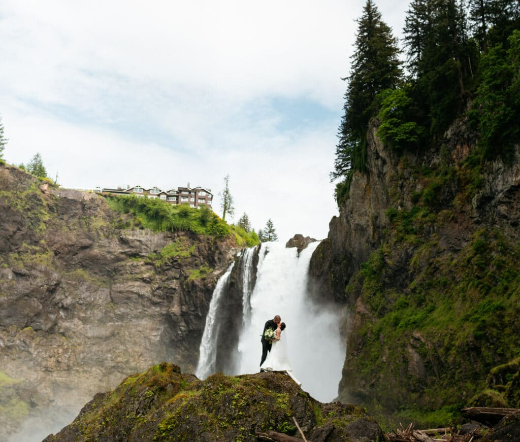Couple kisses in front of snoqualmie falls during salish lodge wedding