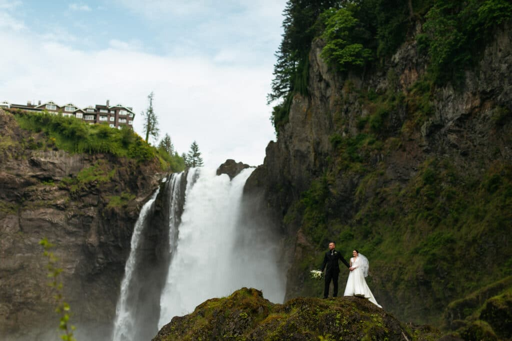 Couple stands in front of snoqualmie falls during salish lodge wedding