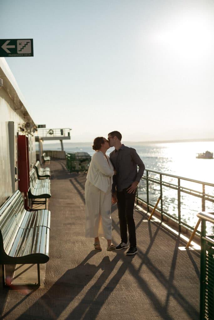 couple kisses on the boat at sunset during bainbridge island ferry wedding