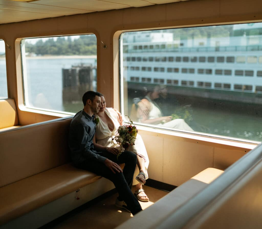 couple sits looking out window during bainbridge island ferry wedding
