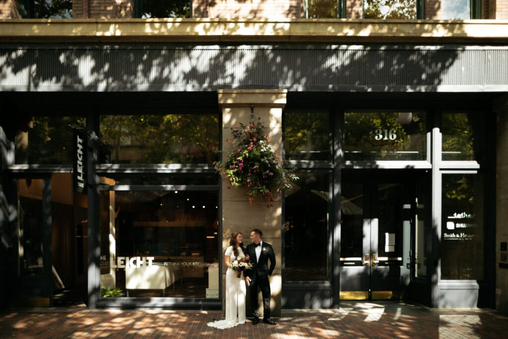 bride and groom pose by building in pioneer square of seattle