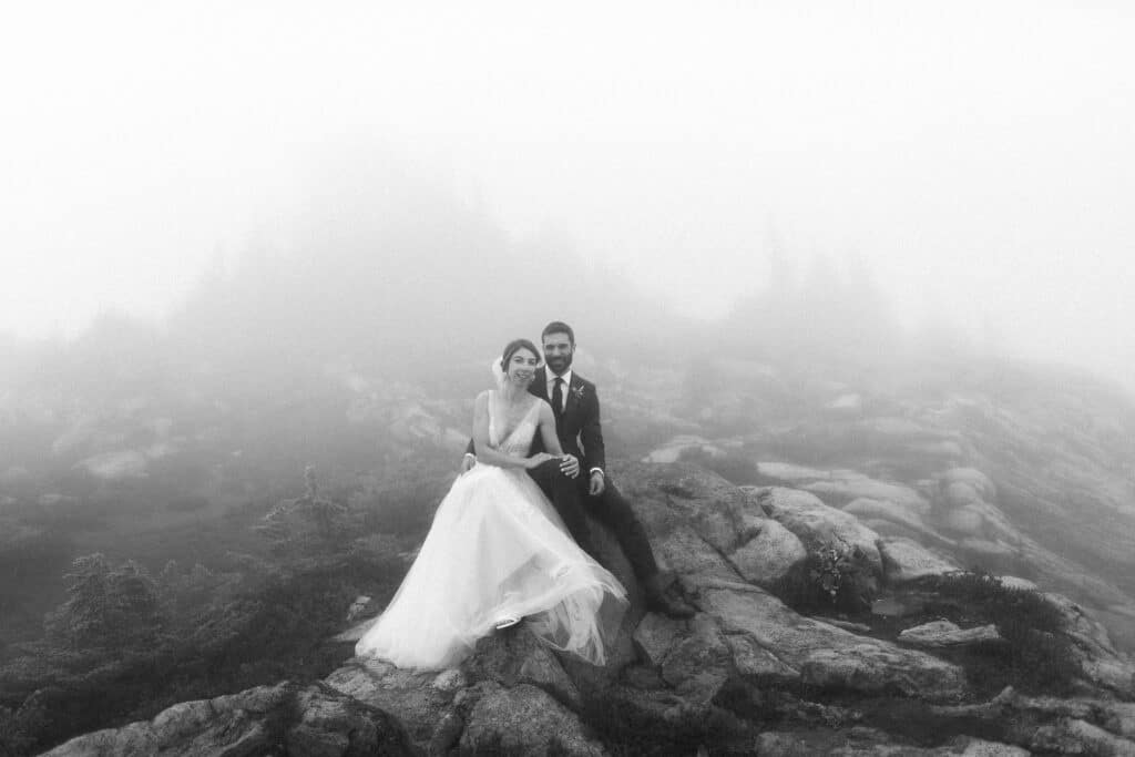 bride and groom sit on a rock during their artist point wedding