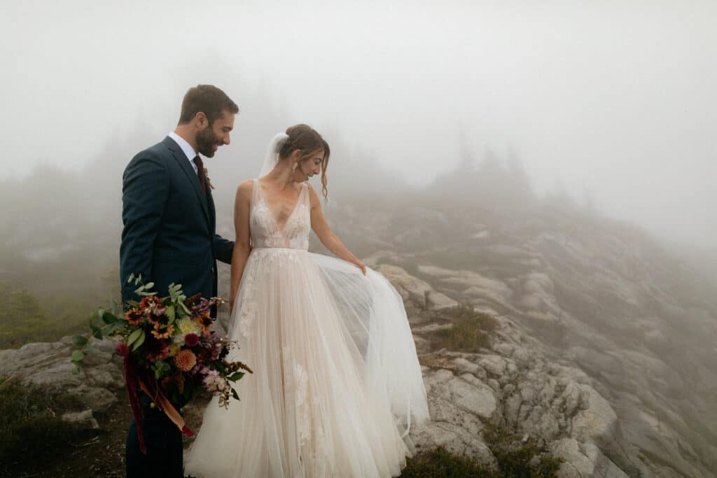 bride and groom hold dress in the fog during artist point wedding