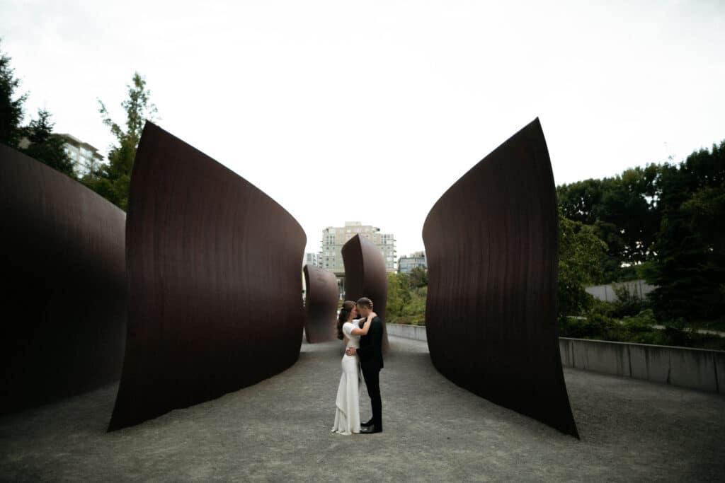couple kisses between art at olympic sculpture park wedding