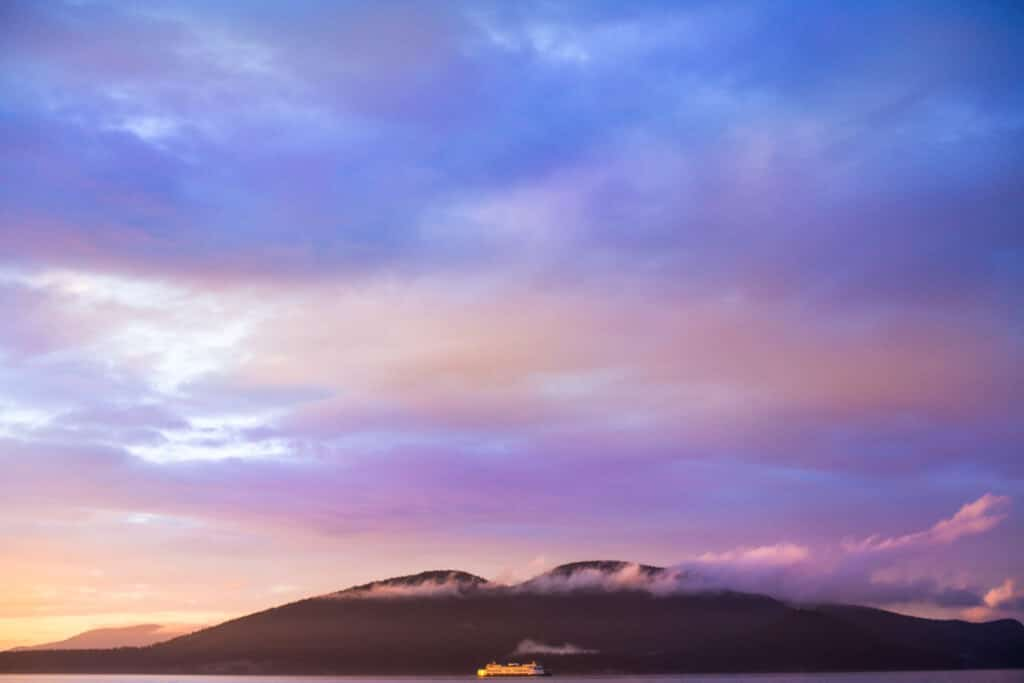 washington state ferry drives across the water during a pink sunset