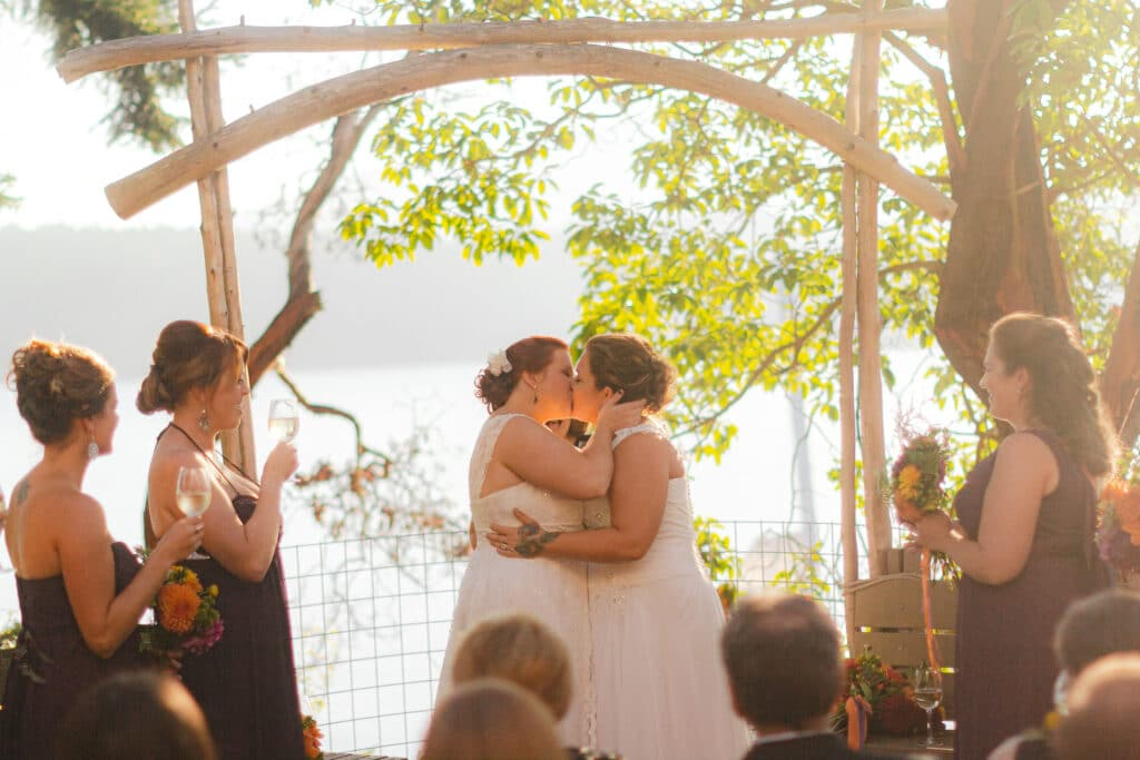 lesbian couple kisses during wedding at Oddfellows hall on orcas island